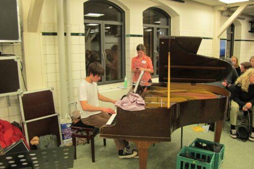 Ventetid inden starten på fællesarrangementet i kantinen. Hyggepianisten er Nicolas (1n)